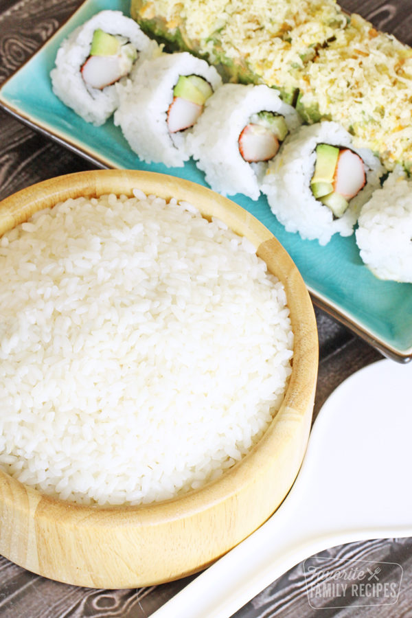 Bowl of sushi rice next to two sushi rolls