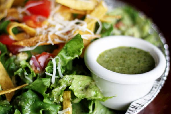 Cafe Rio Cilantro Lime Vinaigrette on the side of a sweet pork salad