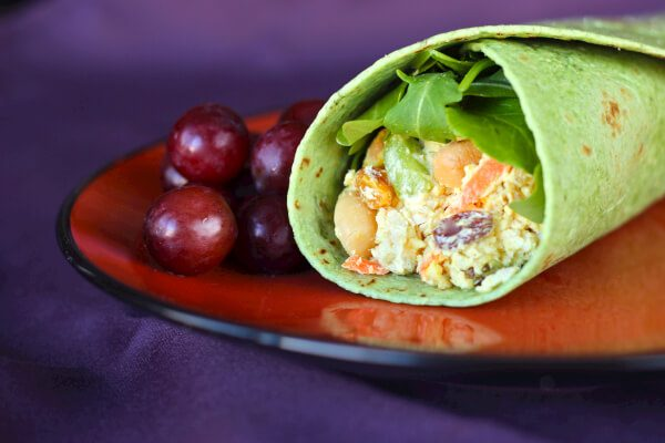Chicken curry wrap on a red plate with grapes