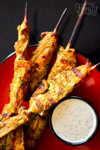 4 Cilantro Thai Chicken Skewers on a red plate with a side of yogurt dipping sauce
