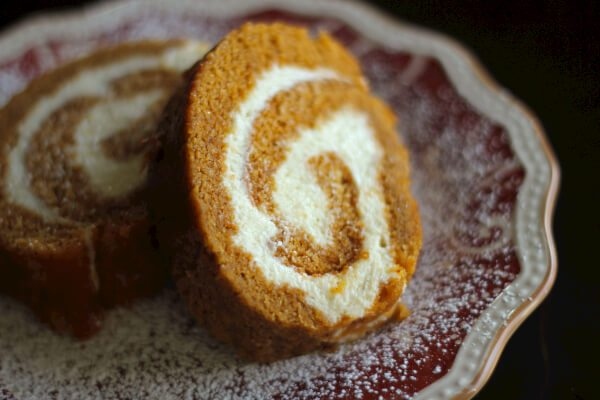 Two slices of pumpkin roll dusted with powdered sugar on a red decorative plate