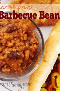 Carolyn's Barbecue Beans in a glass bowl next to a hot dog and chips in the background.