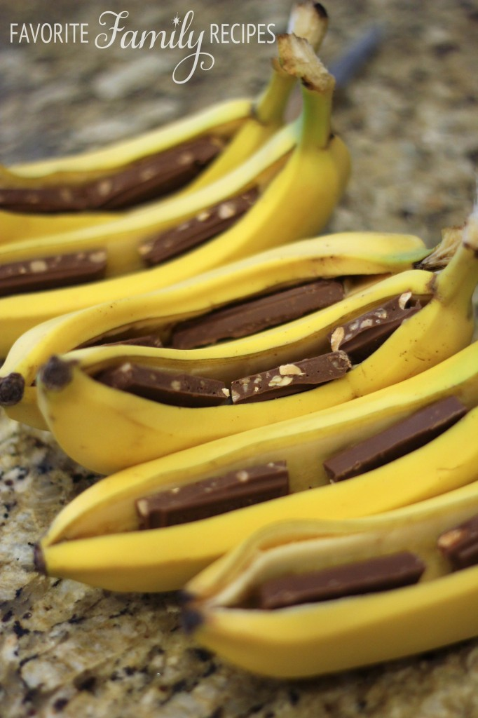 6 bananas sliced down the middle and filled with chocolate on a countertop.