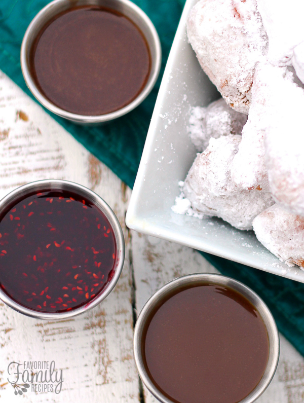 Beignets in a white bowl and sauces on the side.
