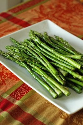 Bright green roasted asparagus on a square white platter
