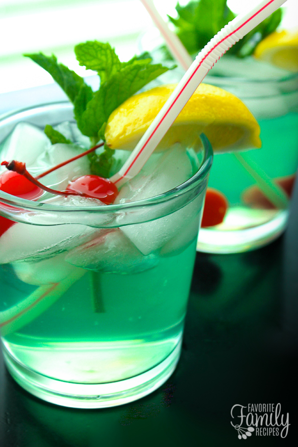 Mint Julep with lime and lemon juice, mint, and garnished with maraschino cherries, lemon wedge, and mint leaf