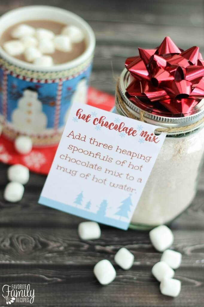 Hot Chocolate Mix in a mason jar with a mug of hot chocolate in the background.