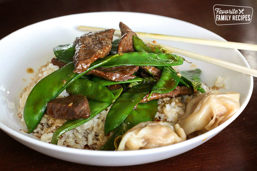 Beef and Snow Peas over rice in a large bowl with chopsticks on the side