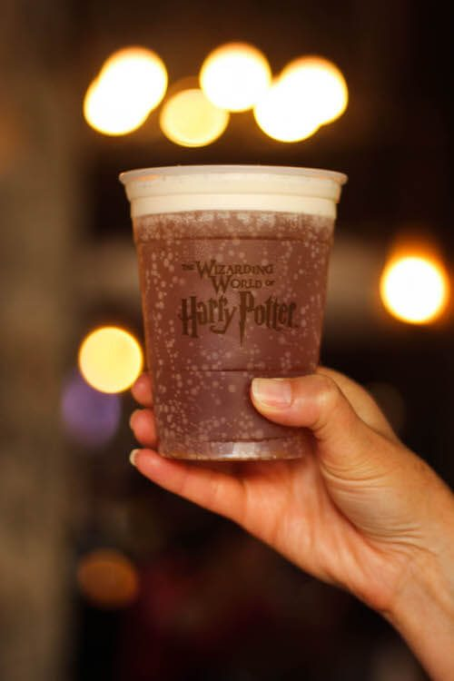 Someone holding up a cup of Harry Potter Butterbeer