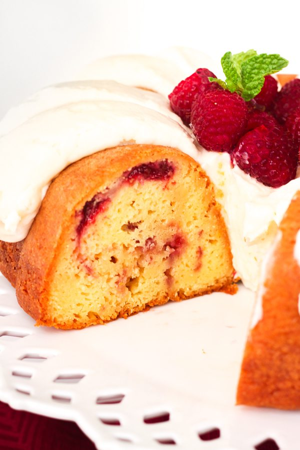 White Chocolate Raspberry Bundt Cake with a slice taken out of it.