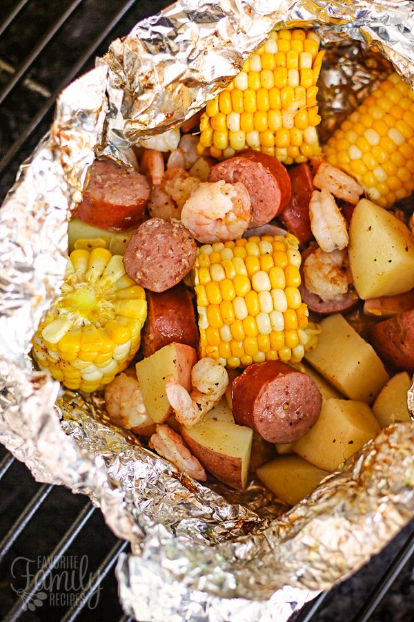 Cajun Shrimp Foil Packets on the grill with shrimp, corn on the cob, sausage, and potatoes