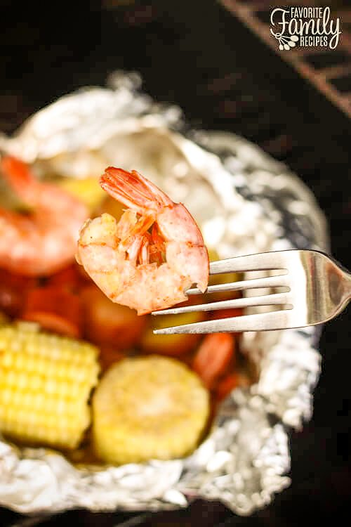 Cajun shrimp on a fork with Cajun Shrimp Foil Packets on the grill in the background