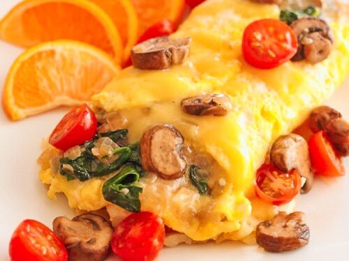 Veggie Omelet on a plate with sliced oranges