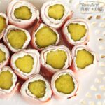 Several Ham and pickle roll ups from above on a white plate.
