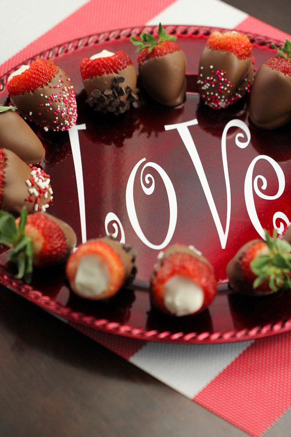 Cheesecake Stuffed Chocolate Dipped Strawberries in a circle on a plate that says love.