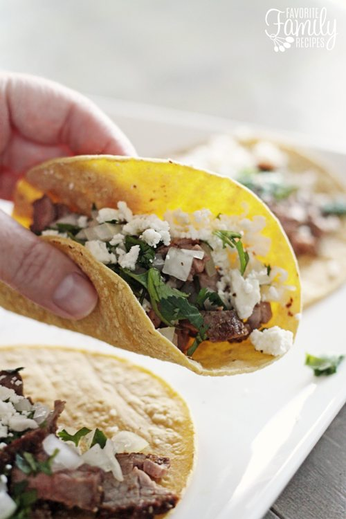 Grilled Steak Street Tacos with one being held up closer to the camera.