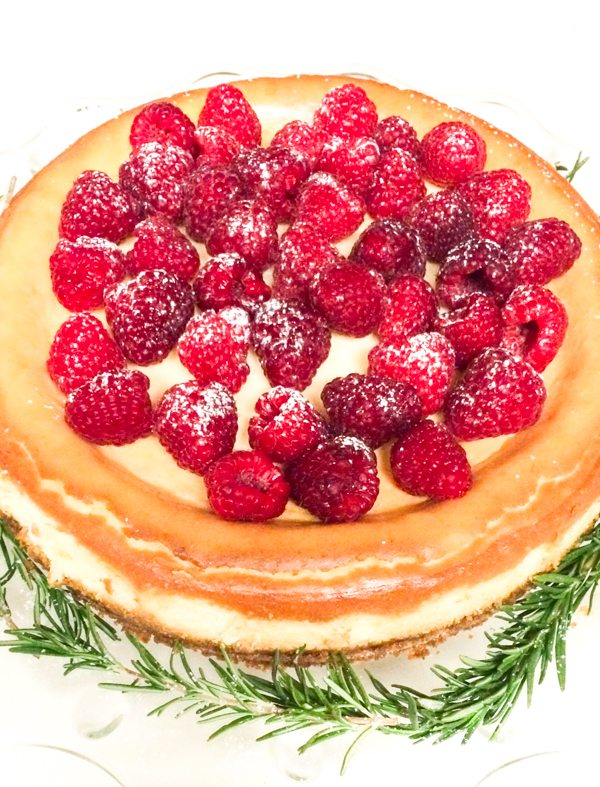 Full Cheesecake covered in raspberries and powdered sugar