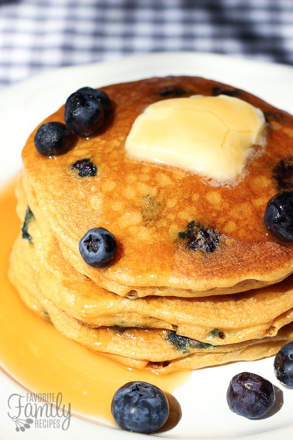 Whole Wheat Blueberry Pancakes served with butter, syrup, and fresh blueberries on a white plate