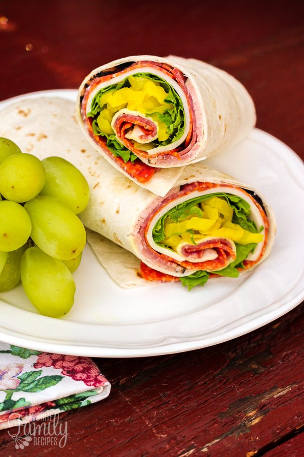 Zesty Italian Lunch Wrap with pepperoni, salami, lettuce, banana peppers and provolone cheese on a lunch plate with grapes