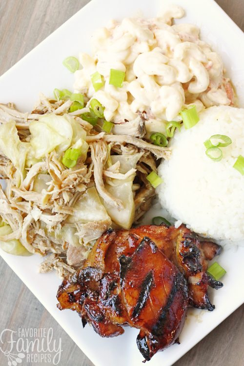 Grilled Hawaiian teriyaki chicken with white rice, macaroni salad, and pork on the side all on a white plate.