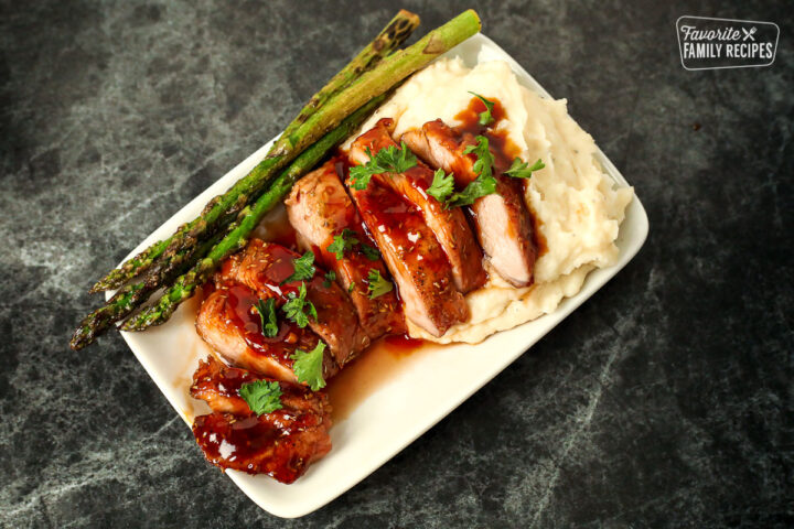 Plate with mashed potatoes, asparagus, and sliced pork tenderloin