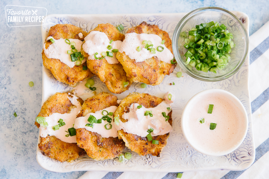 Six Cheesy Potato Cakes on a platter with sauce and green onions on the side