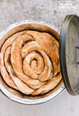 A Cinnamon Roll baked in a Dutch Oven with the Dutch Oven lid on the side