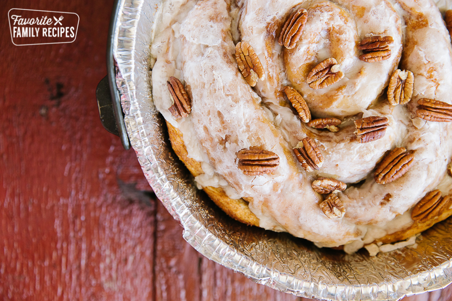 A Dutch Oven Cinnamon Roll with a glaze and pecans on top