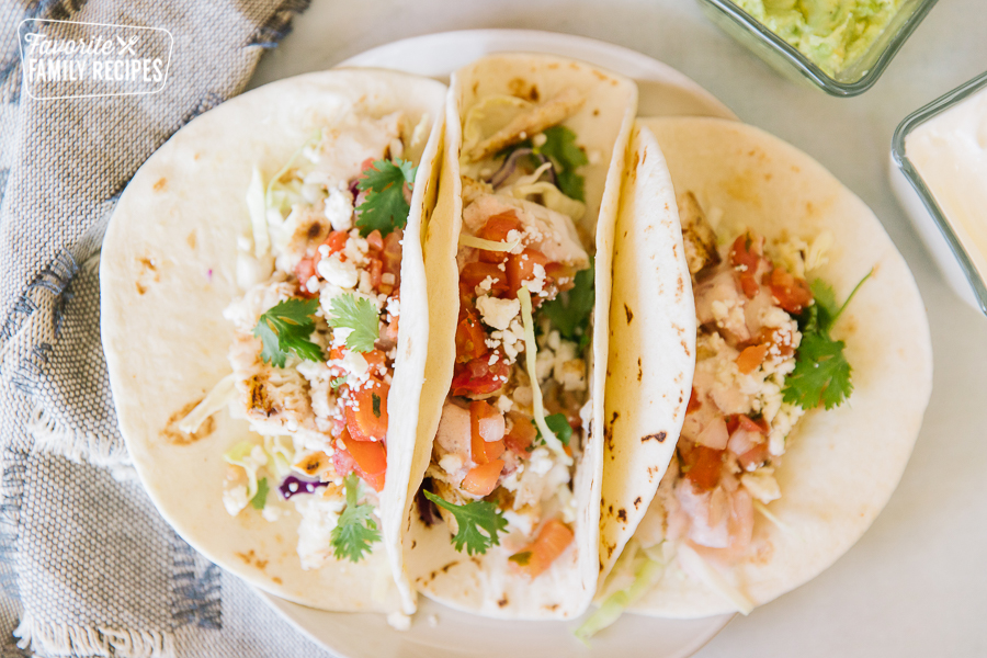 Three Grilled Mahi Mahi Fish Tacos on a platter with pico de gallo, cilantro, and cheese