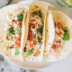 Grilled Mahi Mahi Fish Tacos on a plate with condiments on the side