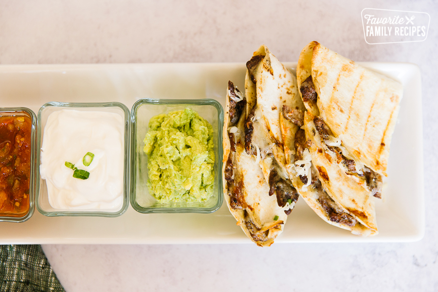 A tray of Grilled Steak Quesadillas with salsa, sour cream, and guacamole in square dishes on the side