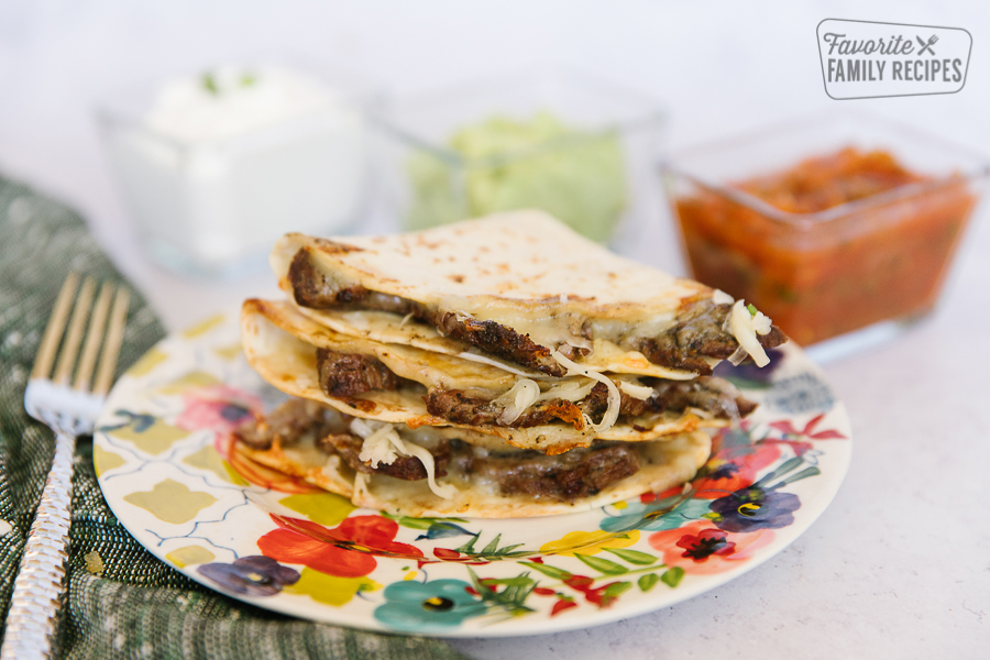 A stack of three Grilled Steak Quesadillas on a floral plate with salsa, guacamole, sour cream on the side