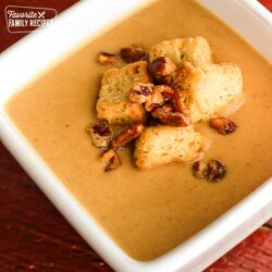 Creamy Butternut Squash Soup topped with croutons in a white square bowl.