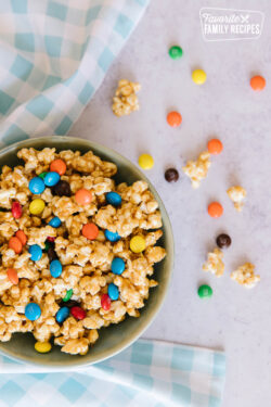 Peanut Butter Popcorn in a bowl surrounded by a blue gingham napkin