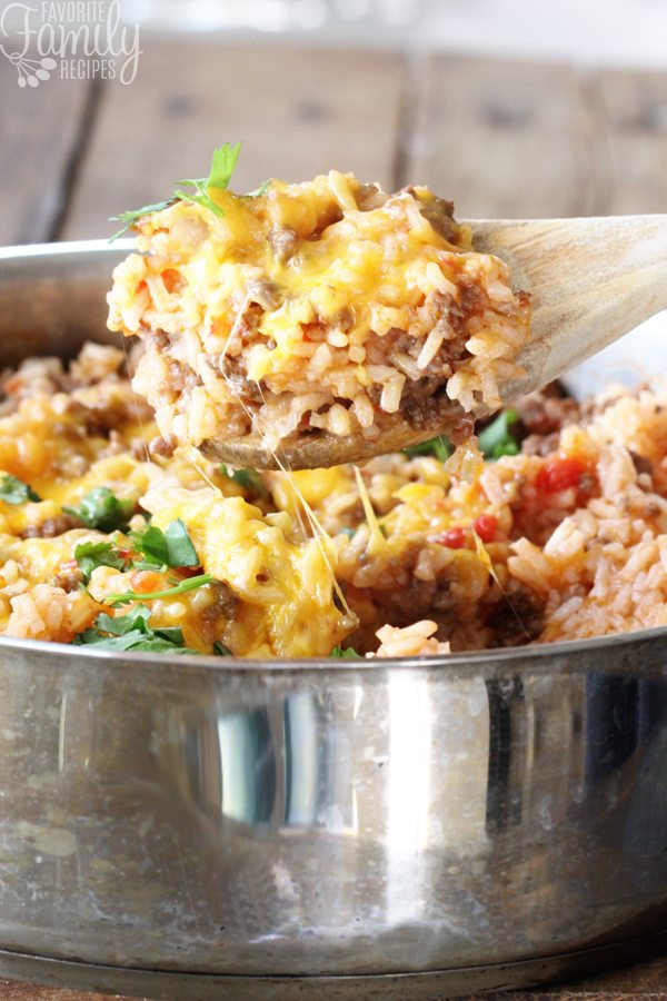 Cheesy Beefy Rice Skillet with a spoon scooping out some rice.