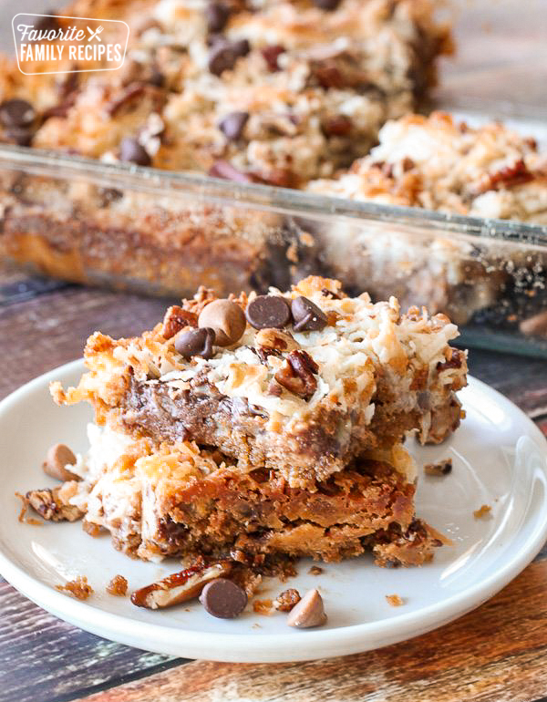 Side shot of a plate of cookie bars with a pan of cookie bars behind