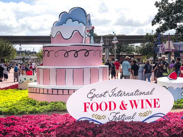 Remy from Ratouille on top of a pink decorated cake at the entrance to the Epcot Food and Wine Festival