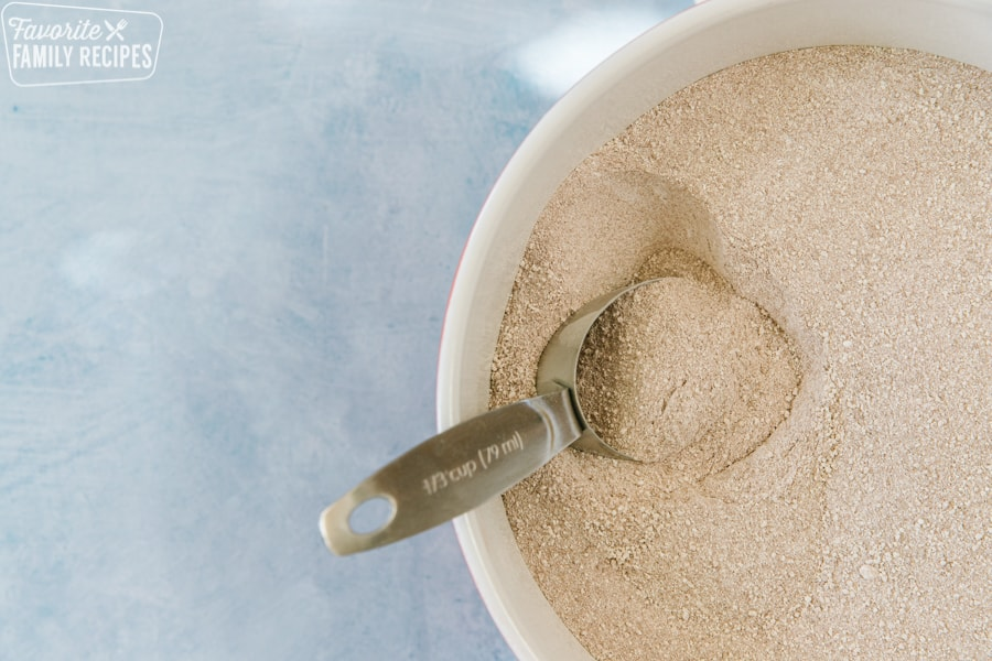 Hot cocoa mix in a big bowl with a scoop in the mix