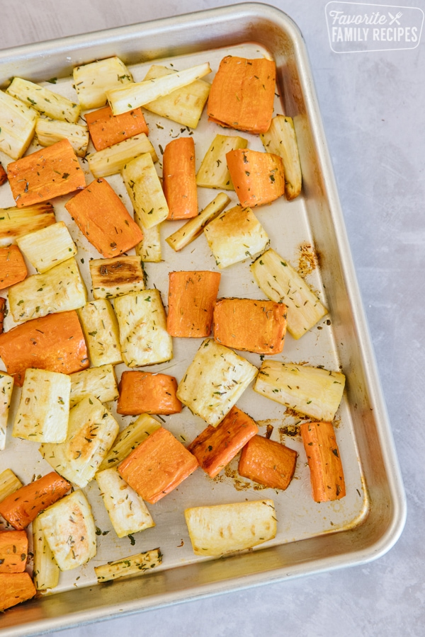 Roasted parsnips and carrots sprinkled with rosemary on a baking tray