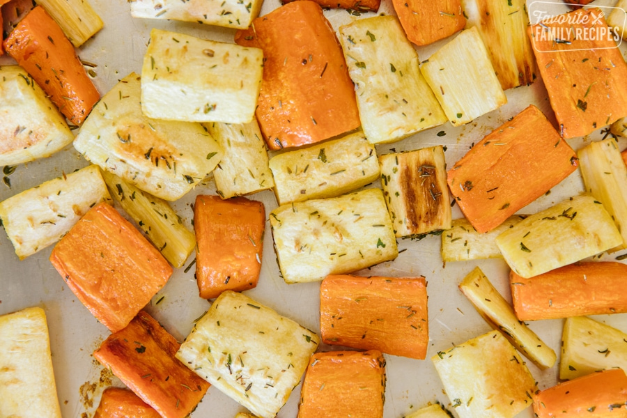 A close up view of roasted parsnips and carrots on a roasting tray