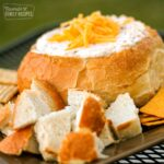 Warm Bacon Cheese Dip in a Sourdough loaf surrounded with bread pieces and crackers for dipping