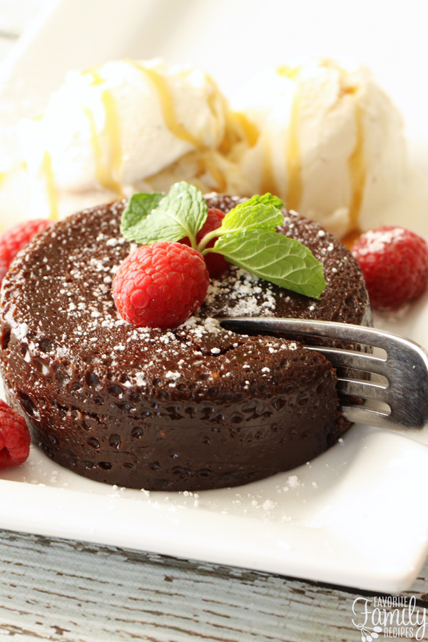 Side view of chocolate lava cake topped with raspberries.