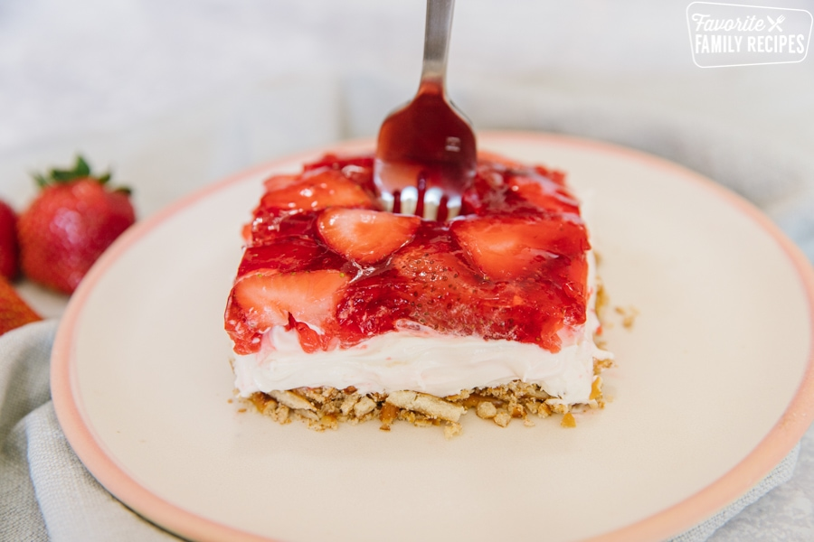 A slice of strawberry pretzel salad on a white plate with a fork sticking up from the middle