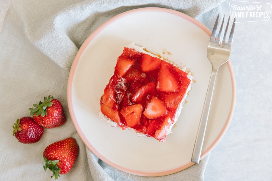 Strawberry pretzel salad on a serving plate with fresh strawberries on the side