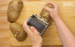 Parboiled potatoes being peeled for hash browns