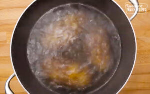 Potatoes parboiling in a pot for has browns