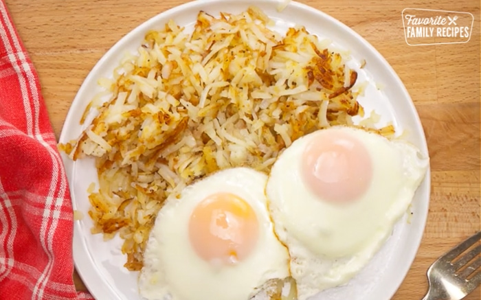 Two fried eggs with homemade hash browns on the side