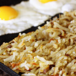 Perfectly browned hash browns served with two sun side up eggs.