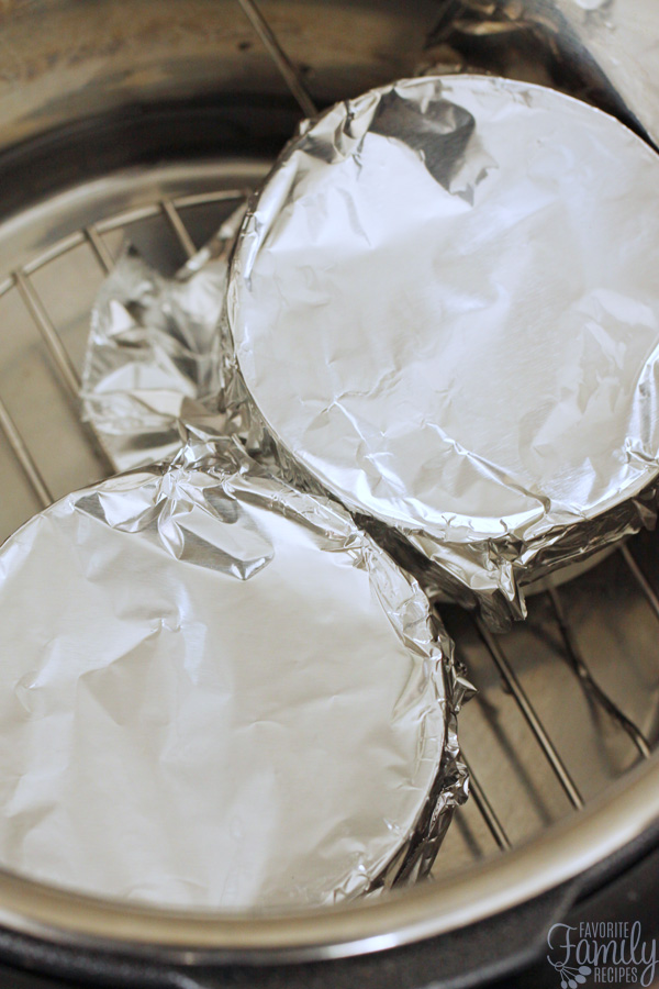 Two ramekins filled with lemon custard and covered with tin foil sitting inside an Instant Pot