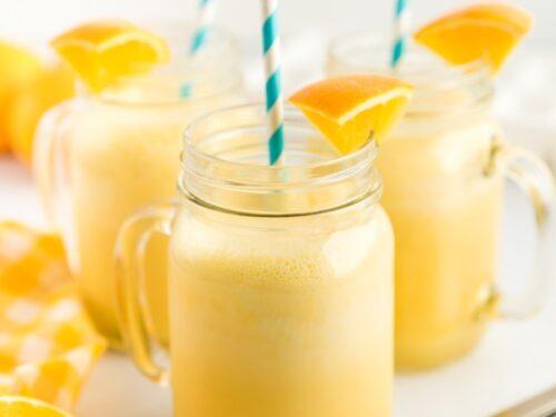 Three clear mugs full of orange julius with a blue straw and orange slice garnishes